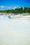 Tropisk vit sandstrand med gröna palmträd och parkerade fiskebåtar i sanden Exotiskt öparadis Royaltyfria Bilder