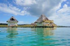 Tropiska bungalower över vatten med halmtäcker taket Arkivfoto