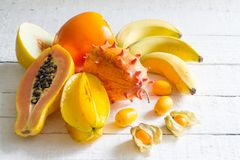 Tropiska exotiska frukter på vita plankor gör sammandrag stilleben Arkivbild
