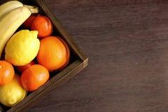 Tropiska frukter i träkorg på bästa sikt för tabell med kopieringsutrymme Saftiga mandariner, apelsin, citron och banan Arkivfoton