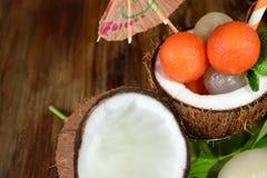 Tropiska frukter: longanen och papayaen boll-formade stycken ligger i kokosnöt Royaltyfria Bilder