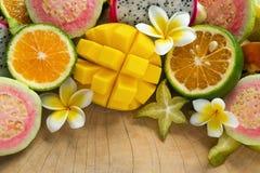 Tropiska frukter mango, tangerin, guava, drakefrukt, stjärnafrukt, sapodilla med blommor av plumeria på träbakgrunden Arkivfoton