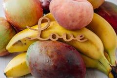 Tropiska frukter med ordförälskelse på den vita tabellen Arkivfoto
