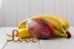 Tropiska frukter med ordförälskelse på den vita tabellen Royaltyfri Foto