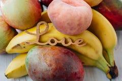 Tropiska frukter med ordförälskelse på den vita tabellen Royaltyfri Fotografi
