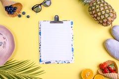 Tropiska frukter och bär och en gömma i handflatanfilial på en gul bakgrund Fritt utrymme för text på ett vitt bräde i mitten Royaltyfria Bilder