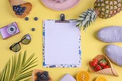 Tropiska frukter och bär och en gömma i handflatanfilial på en gul bakgrund Fritt utrymme för text på ett vitt bräde i mitten Arkivfoto