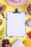 Tropiska frukter och bär och en gömma i handflatanfilial på en gul bakgrund Fritt utrymme för text på ett vitt bräde i mitten Royaltyfria Foton