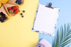Tropiska frukter och bär på en guling- och blåttbakgrund Tillbehör för ferier och avkoppling Vitt bräde med ett krabbt Arkivfoto