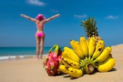 Tropiska frukter och en kvinna i en bikini som solbadar på stranden på havsbakgrund. Arkivbilder