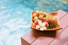Tropiska frukter och plmeria i mjuk fokus på trämagasinet nära simbassäng Royaltyfri Foto