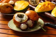 Tropiska frukter: passionfrukt, rambutan och mango arkivbild