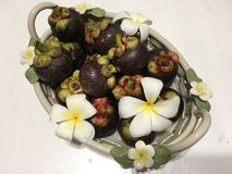 Tropiska mangosteenfrukter i den keramiska korgen som dekoreras med frangipaniblommor arkivbilder