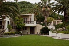 Tropiska strandhousewhitpalmträd och en trevlig gräsmatta Arkivfoton