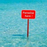 Tropiskt hav för turkos med det röda tecknet som här säger paradis Arkivbild