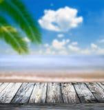 Tropiskt hav och strand med palmblad och trägolvet arkivfoton