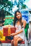 Tropiskt julbegrepp Ung kvinna i den Santa Claus pulkan med skinande färgrika gåvor Fotografering för Bildbyråer