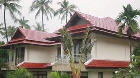 Tropiskt regn tappar att falla på palmbladen i ön Koh Samui, Thailand Ändringsfokus till det härliga huset från regn arkivfilmer