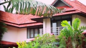 Tropiskt regn tappar att falla på palmbladen, och ändringar fokuserar till det härliga huset på bakgrund i ön Koh Samui lager videofilmer
