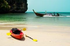 Tropiskt strandlandskap med det röda kanotfartyget på havet royaltyfria bilder