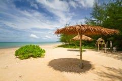 Tropiskt strandlandskap med ett slags solskydd Arkivbild