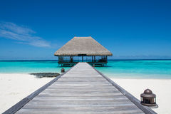Tropiskt strandlandskap med träbron och huset på vattnet på Maldive Fotografering för Bildbyråer