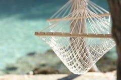 Tropiskt strandsemesterbegrepp med ett hängmatta- och turkosvatten Royaltyfri Fotografi