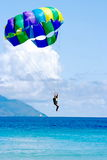 Tropocal sea vacation landing. This is the hot summer tropical day. Parachuter is landing into the fresh water of the paradise beach. The sky area is free for Stock Image
