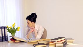 Troppa giovane donna sonnolenta stanca del lavoro che si siede al suo scrittorio con i libri archivi video