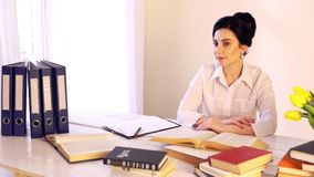 Troppa giovane donna sonnolenta stanca del lavoro che si siede al suo scrittorio con i libri video d archivio