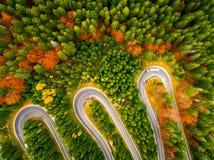 Troquez l'enroulement vers le haut de sa manière sur une route sinueuse par l'automne colorée Photographie stock libre de droits