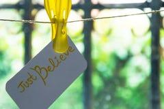 ` Tror precis `-kortet som hänger på tråden, bakgrund - tänd bak stängerna Begrepp - tro alltid Royaltyfri Foto