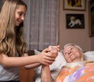 Troskliwa dziewczyna trzyma starego lady& x27; s ręki Zdjęcia Stock