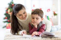Troskliwa matka czyta jej dziecko ciekawą książkę na wigilii fotografia stock