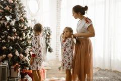 Troskliwa matka splata jej córki małego warkocz podczas gdy drugi córka dekoruje nowego roku drzewa w świetle wygodnym obraz royalty free