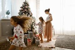 Troskliwa matka splata jej córki małego warkocz podczas gdy drugi córka dekoruje nowego roku drzewa w świetle wygodnym obraz stock