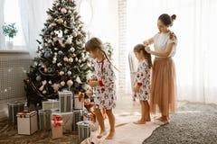 Troskliwa matka splata jej córki małego warkocz podczas gdy drugi córka dekoruje nowego roku drzewa w świetle wygodnym fotografia royalty free
