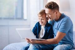 Troskliwe ojca dopatrywania kreskówki z jego synem na laptopie Zdjęcia Royalty Free