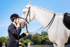 Troskliwy żeński jeździec kocha jej białego konia ogromnie zdjęcia stock