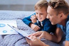 Troskliwy ojciec dokładnie badać wydruk z mapami z ojcem zdjęcie stock