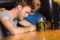 Troskliwy przyjaciel pociesza wzburzonego mężczyzna Fotografia Stock