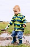 Troszkę bawić się w błotnistej kałuży dziecko Fotografia Stock