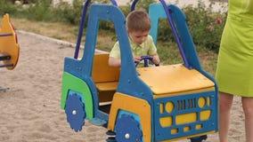 Troszkę chłopiec bawić się na boisku w zabawkarskim samochodzie, jego matka stoi następnie zbiory wideo