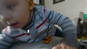 Troszkę chłopiec bawić się z jego zabawkami na karle Berbeć chłopiec bawić się z zabawkarskimi samochodami zbiory wideo
