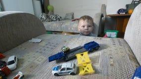 Troszkę chłopiec bawić się z jego zabawkami na karle Berbeć chłopiec bawić się z zabawkarskimi samochodami zbiory