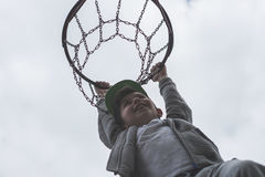 Troszkę chłopiec doskakiwanie i robić cel bawić się streetball, koszykówka Rzuca koszykówki piłkę w pierścionku Pojęcie sport Fotografia Stock