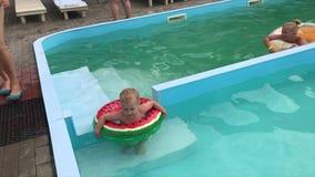 Troszkę chłopiec i nastoletnia dziewczyna baraszkujemy w basenie na nadmuchiwanych okręgach