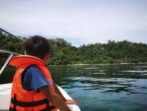 Troszkę chłopiec jest ubranym życie kamizelkę na łodzi dla zbawczych środków ostrożności podczas plenerowej wycieczki zdjęcie royalty free