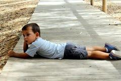 Troszkę chłopiec lying on the beach na drewnianej podłoga zdjęcie royalty free