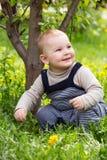 Troszkę chłopiec obsiadanie na trawie Obrazy Stock